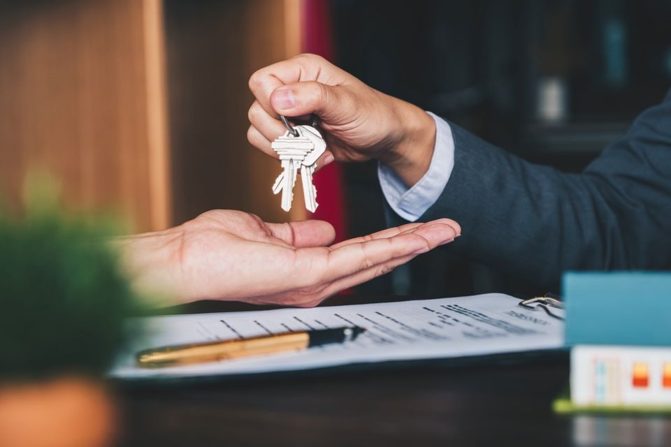 a hand passing a key to another hand